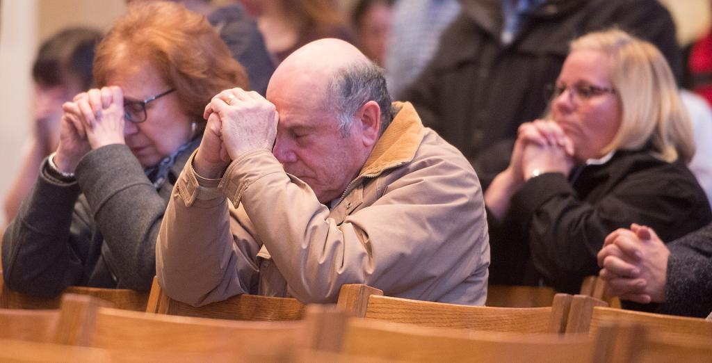 Worshippers pray duringtheMass.