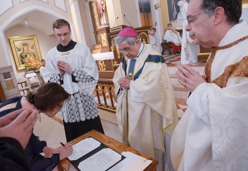 Dr. Elissa Sanchez-Speach signs documents following the Mass. (Courier Photo by John Haeger)