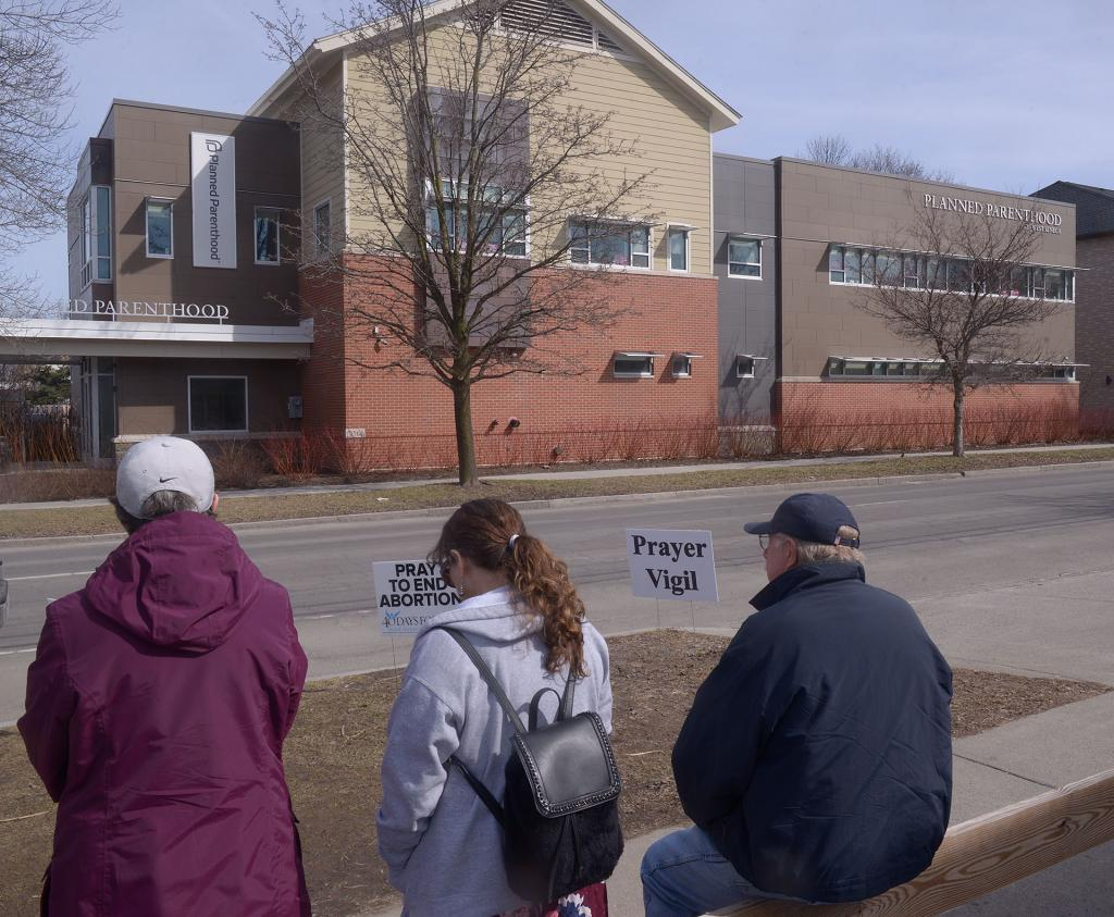 People pray across the street from Planned Parenthood in Ithaca March 27.