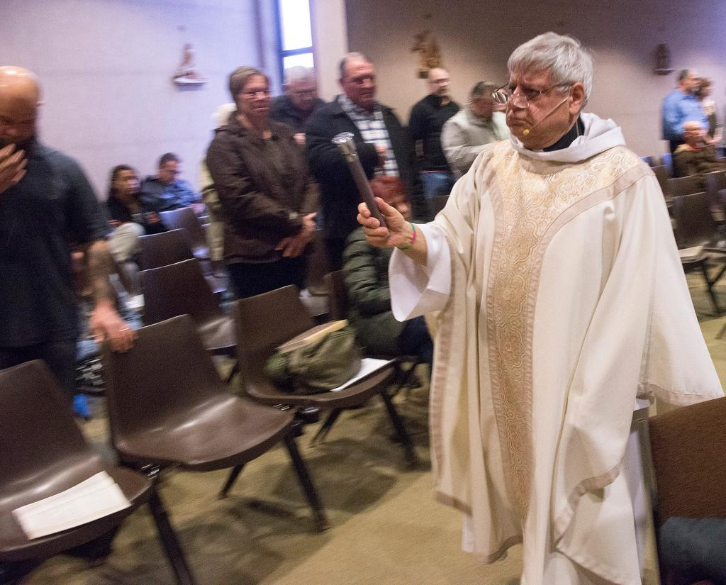 Father Robert Gaudio blesses the couples after they renewed their marriage vows.(Courier Photo by John Haeger)
