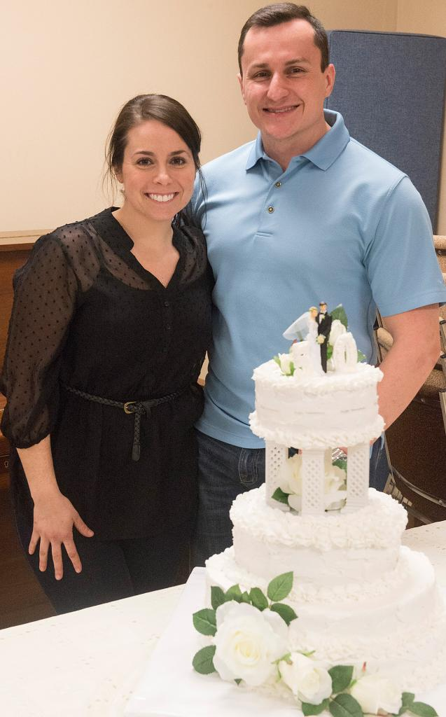 Laura and Jon McGovern pose next to an anniversary cake during a reception that followed the renewal of marriage vows. The McGoverns have been married for nine years.<br /> (Courier Photo by John Haeger)