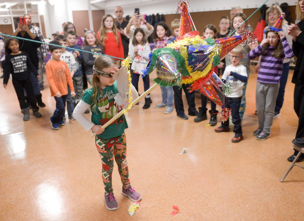 A youth takes a swing at a piñata during Las Posadas at St. James Church Hall in Irondequoit Dec. 17. (Courier photo by John Haeger)