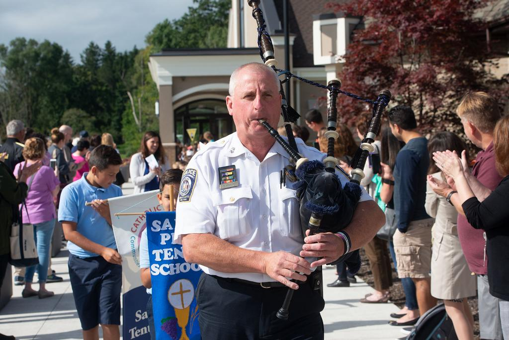 Gates Police Chief Jim VanBrederode plays the bagpipes as he leads students back to school after the Mass.