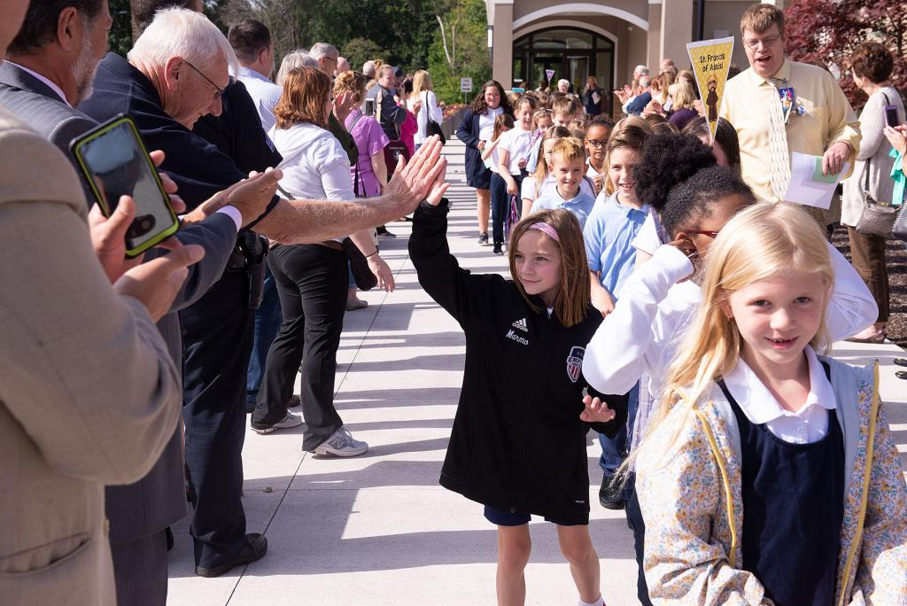 Students receive high fives as they walk back to school.