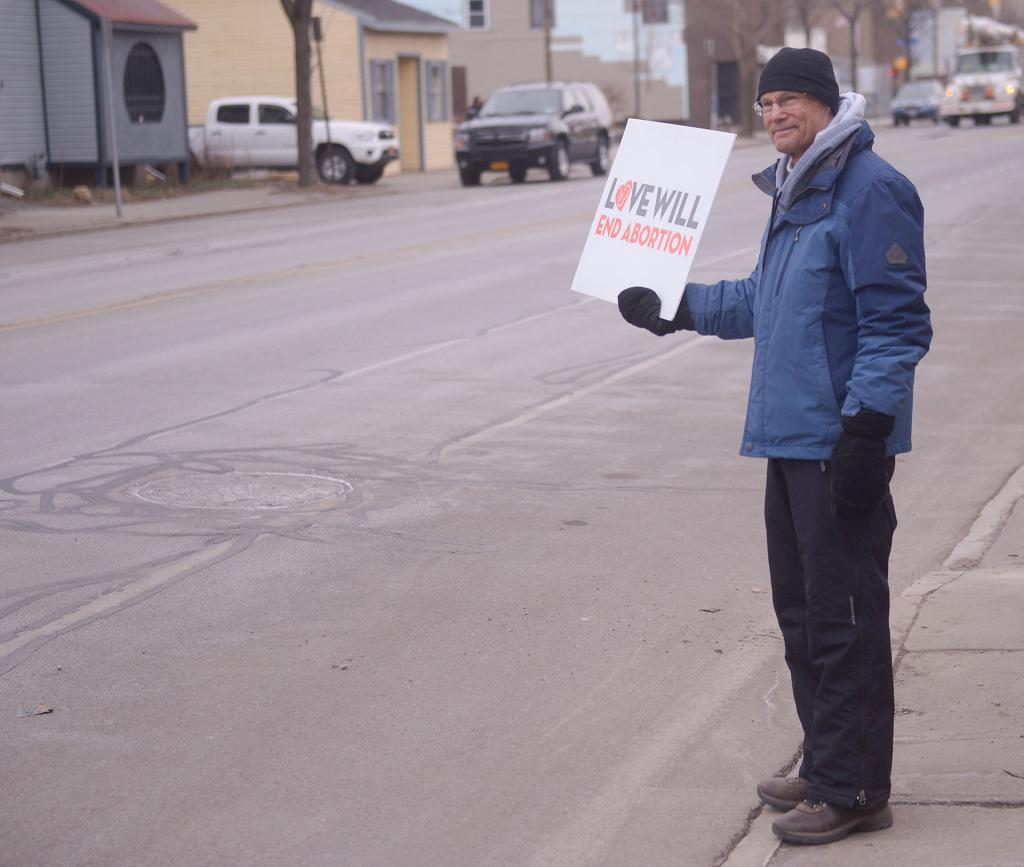 A 40 Days for Life participant holds a sign to as he stands across the street from Planned Parenthood in Rochester March 28.