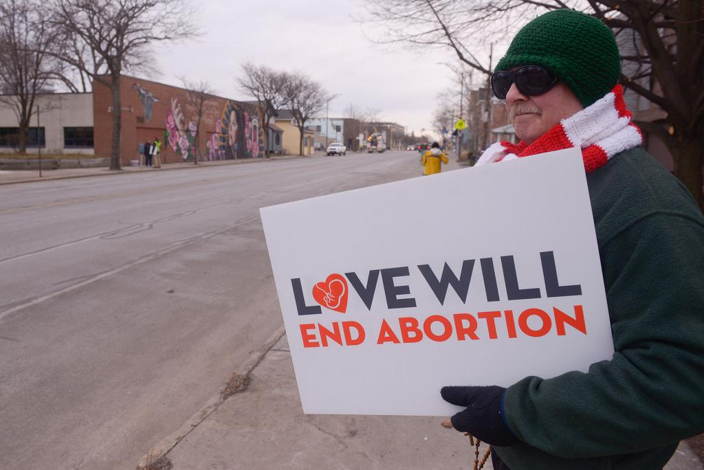 A 40 Days for Life participants stands across from Planned Parenthood in Rochester March 28.