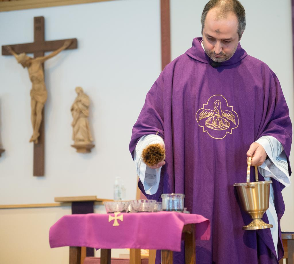 Father Daniel Ruiz-Sierra, parochial administrator at Holy Cross in Freeville, blesses the ashes during Mass on Ash Wednesday, Feb. 14. (Courier photo by John Haeger)