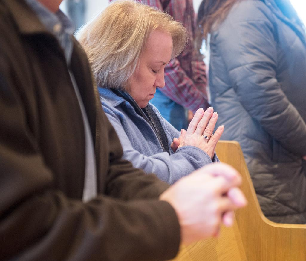 Sharon Buechel prays after receiving ashes at Holy Cross in Freeville. (Courier photo by John Haeger)