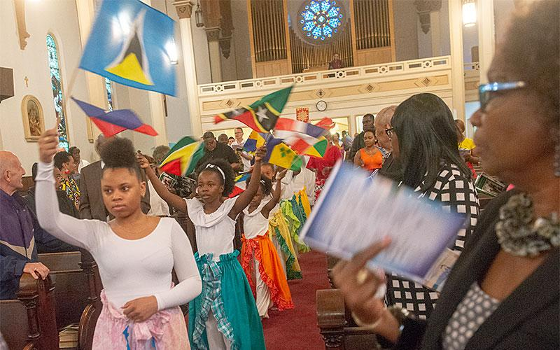 Members of the Immaculate Conception Junior Liturgical Dancers carry the flags of Caribbean nations as they process into Immaculate Conception Church June 2 the annual Caribbean Mass.
