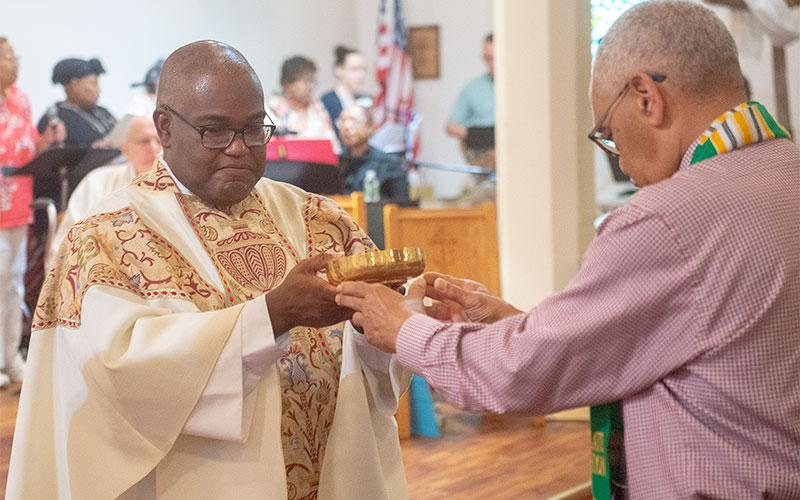 Father Walker receives the gifts from George Fontenette.