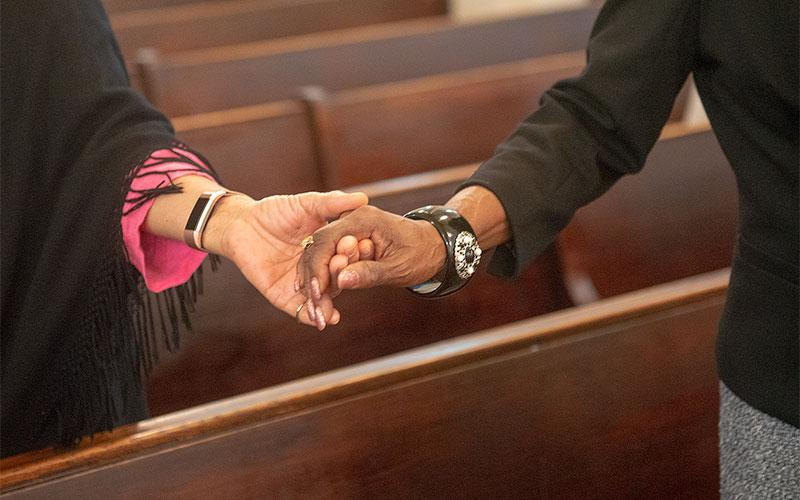 People hold hands as they pray.