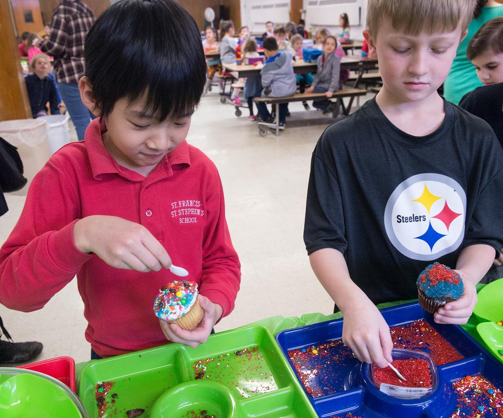 St. Francis-St. Stephen School students William Yu and Thomas Hutteman decorate cupcakes as part of Catholic Schools Week celebrations Jan. 29.