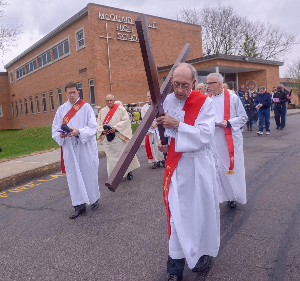 Deacon John Crego carries a wooden cross as he leads the procession to the second station during the Stations of the Cross in Reparation for Abortion.