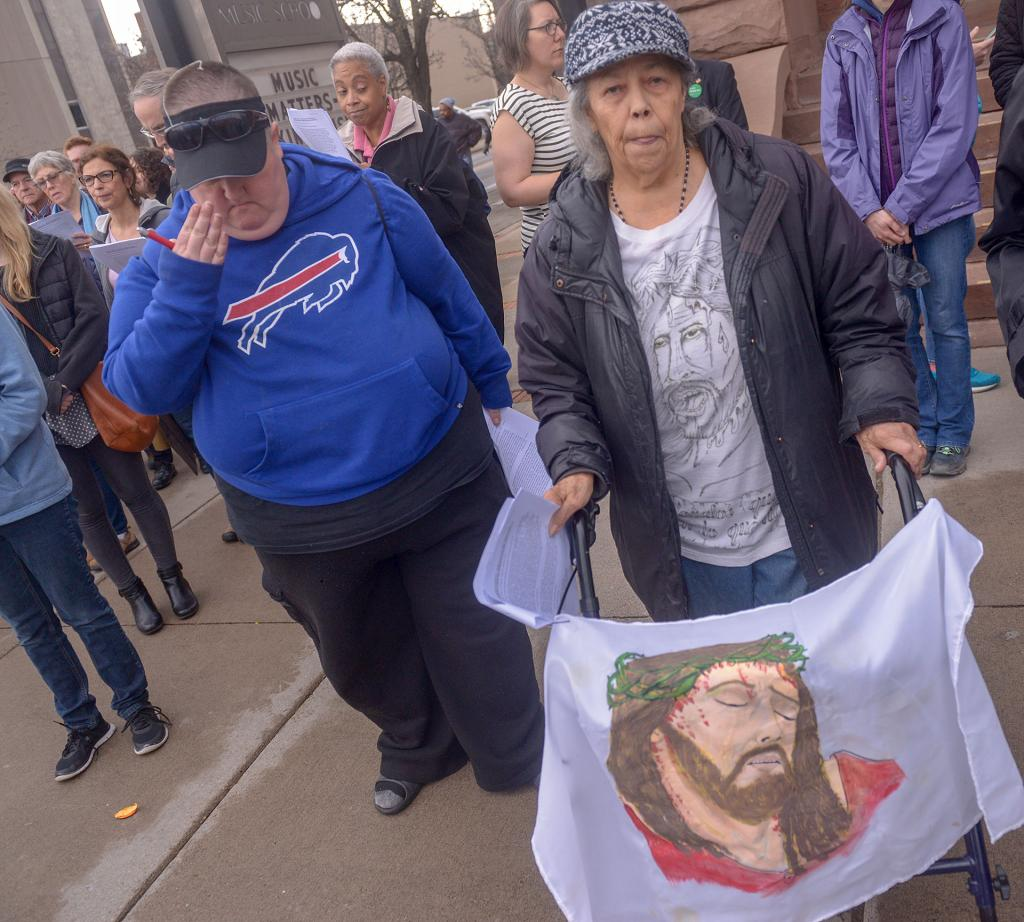 Belen Colon displays a portrait of Jesus during the Stations of the Cross organized by the House of Mercy, St. Joseph's House of Hospitality and Rochester Pax Christi.