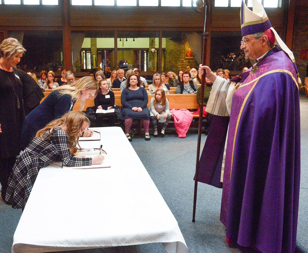 Teagan Matteson of Elmira signs the book of enrollment as Bishop Salvatore R. Matano looks on during the Rite of Election and Call to Continuing Conversion March 10 at St. Mary Our Mother Church in Horsehead.