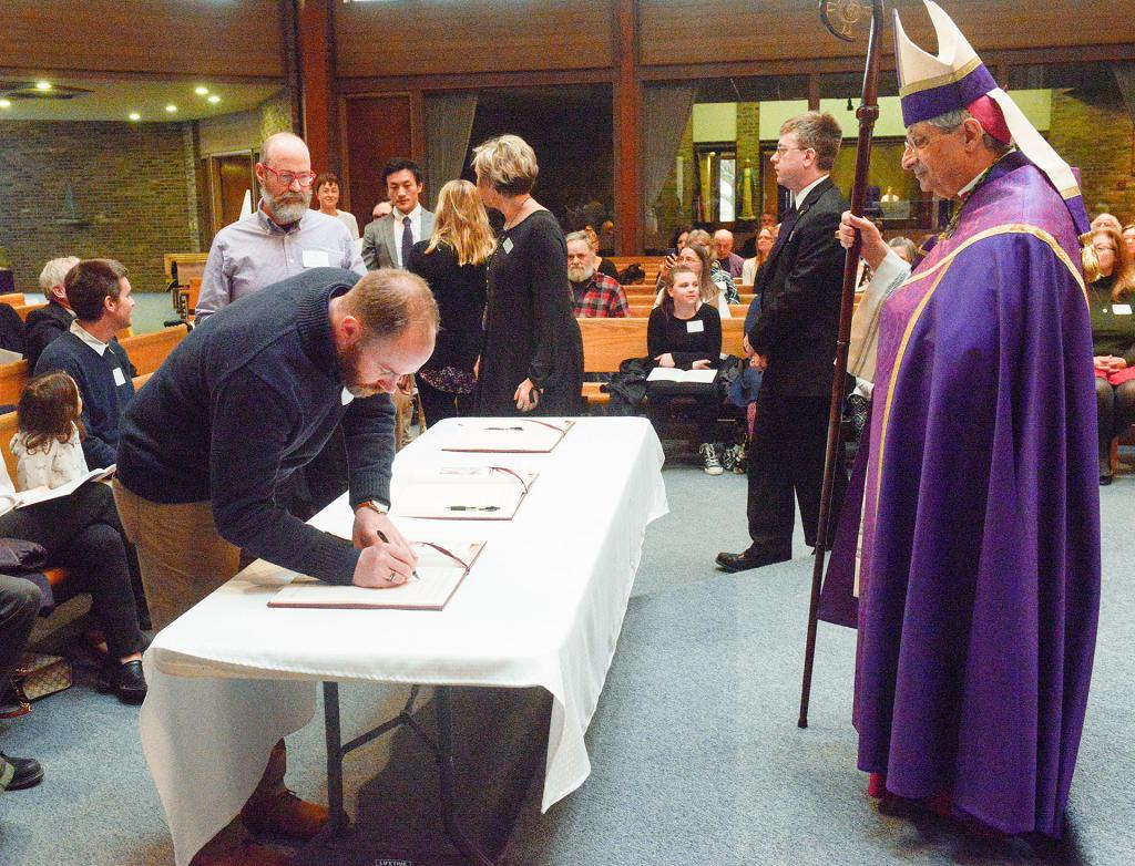 Catechumens sign the book of enrollment as Bishop Matano looks on.