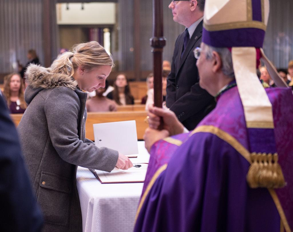 Bishop Salvatore R. Matano looks on as catechumen Bridgette Fletcher of St. Michael Church in Penn Yan signs the Book of the Elect.
