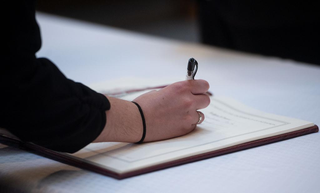 A catechumen signs her name in the Book of Elect.