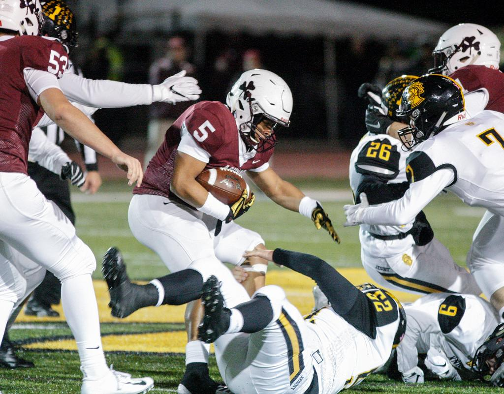 Aquinas' Ruben Torres (5) looks for the hole as he is tripped up by McQuaid's Tim Fournier (52) during the Section 5 Class AA football championship at SUNY Brockport Nov. 3.(Courier Photo by John Haeger)