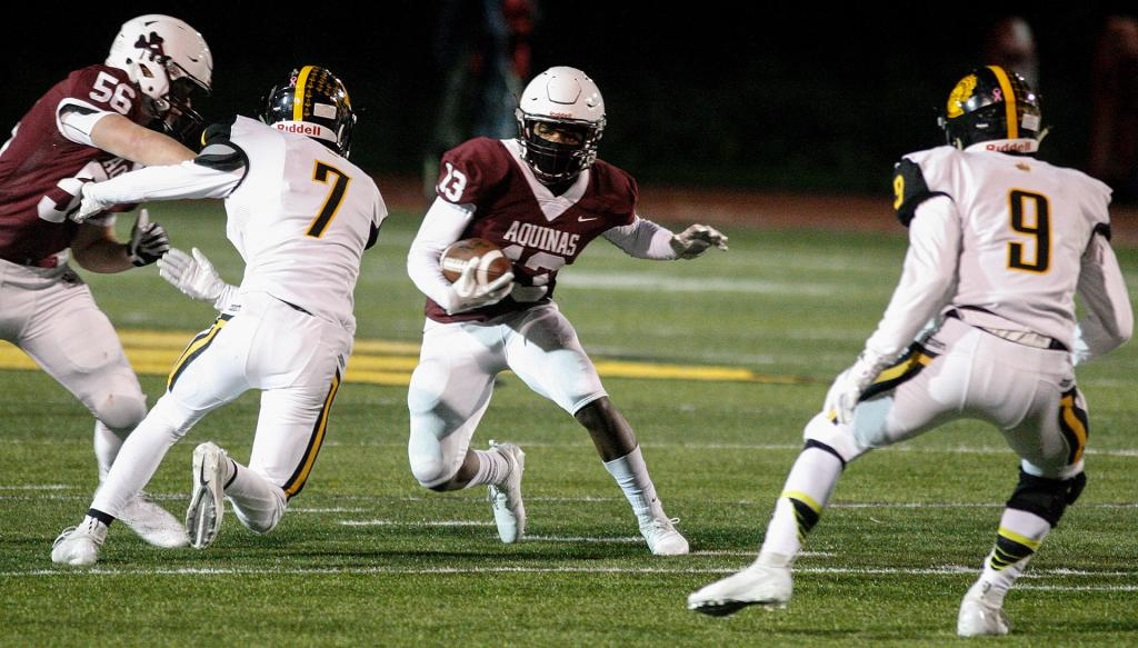 Aquinas' Will Benjamin (13) looks for room to run as McQuaid players move in to defend.<br />(Courier photo by John Haeger)