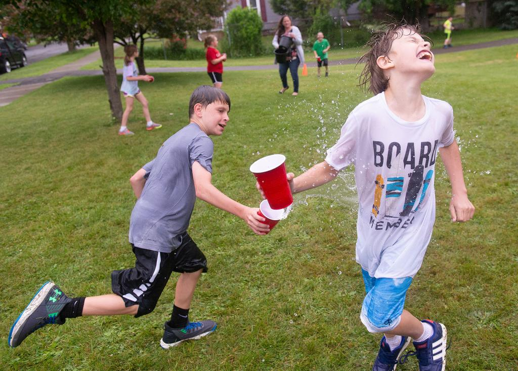 Bobby Sharp (right) reacts as he is splashed with water by classmate Luka Clark during a water relay race at Holy Family School in Elmira as part of the school's annual field day June 13. (Courier photo by John Haeger)