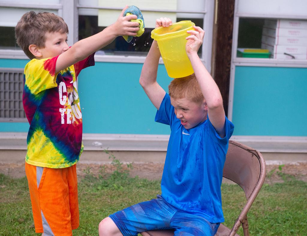 Daniel Cowen squeezes water into a basket as classmate Brock Carr holds the basket on his head as they compete in a relay race at Holy Family School in Elmira June 13. (Courier photo by John Haeger)