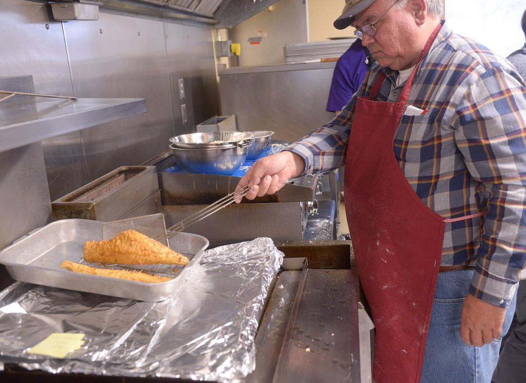 Dave Samuelson cooks fish for a Lenten fish dinner at St. Rita Church in Webster March 22. Over the past 20 years, the event has raised $100,000 to benefit St. Rita School.