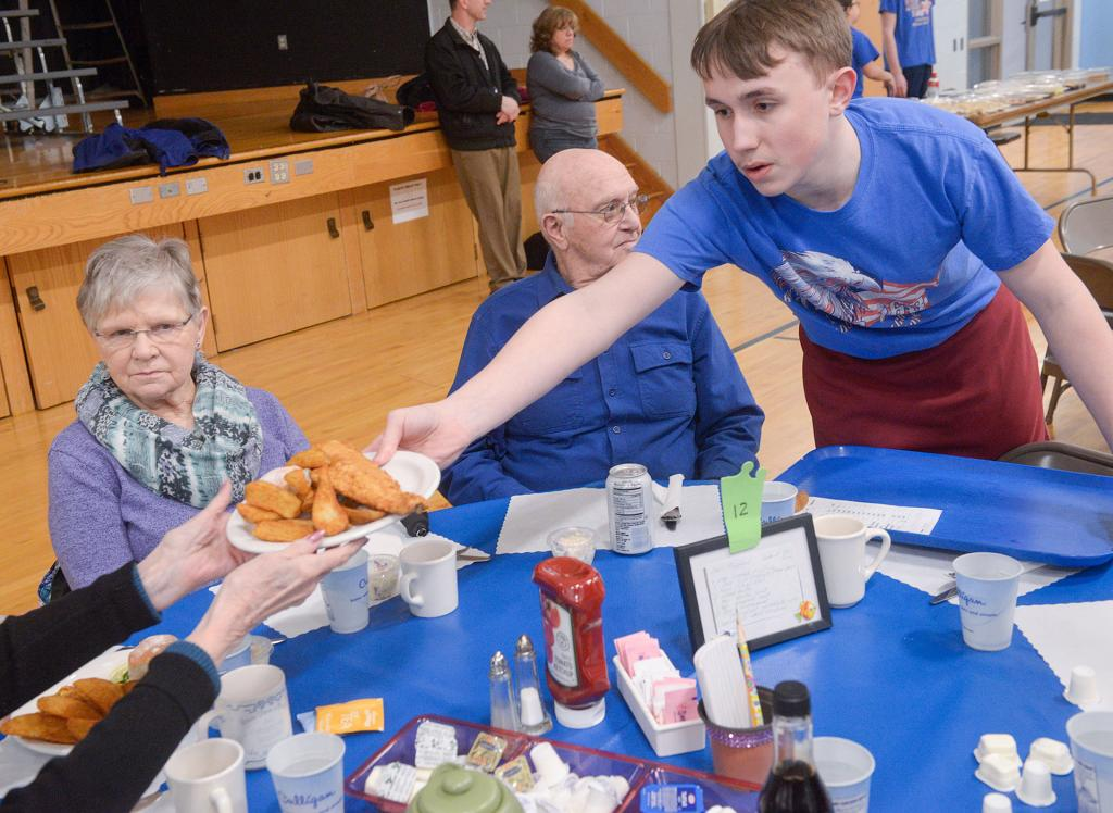 Nathan Chamberlain serves food during the St. Rita Church's fish dinner March 22.