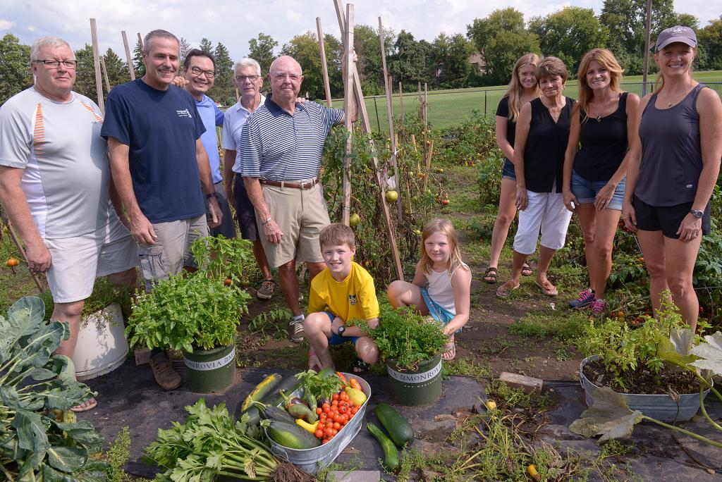 Joe Murphy, Dan Lynch, Father Edison Tayag, Ray Woerner, Bob Belleville, Maddy Lynch, Toni Woerner, Karen Lynch, Gayle Reh, Adam Reh and Anna Reh pose at the Giving Garden at St. Patrick Church in Victor Aug 29. (Courier Photo by John Haeger)