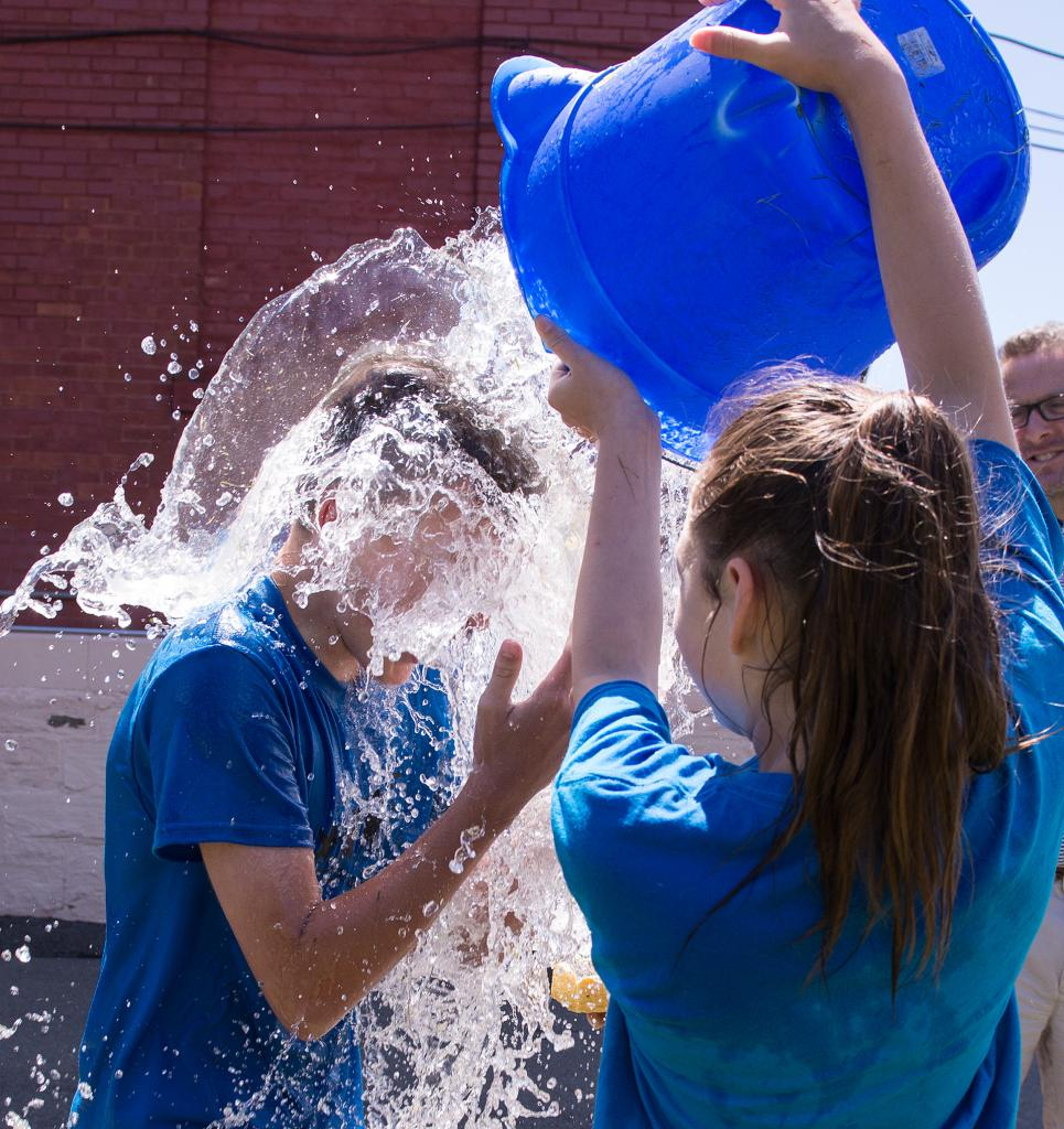 Giuliana Abbey, 11, dumps a bucket of water on Jack Stemerman, 12, during the annual field day at Holy Family School in Elmira June 15.
