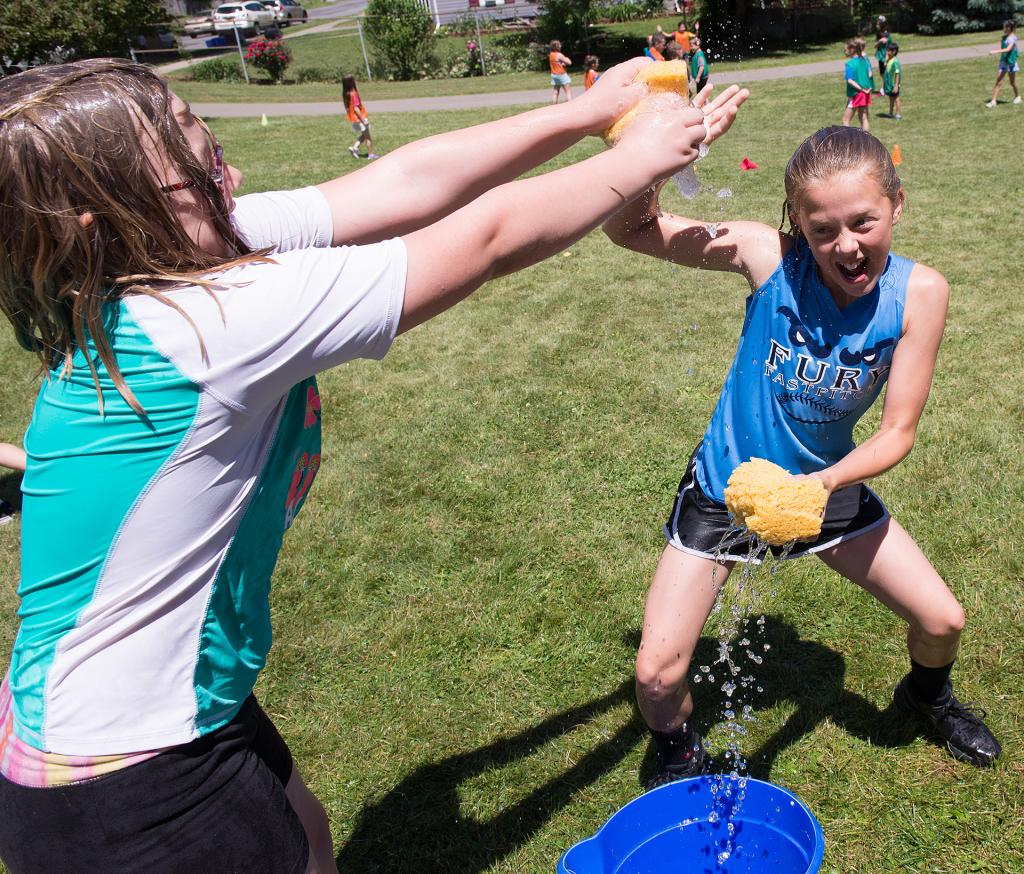 Lillian Cowan, 9, squeezes water onto classmate Ava Sherman, 11, during a game of sponge tag at Holy Family School's the field day event.