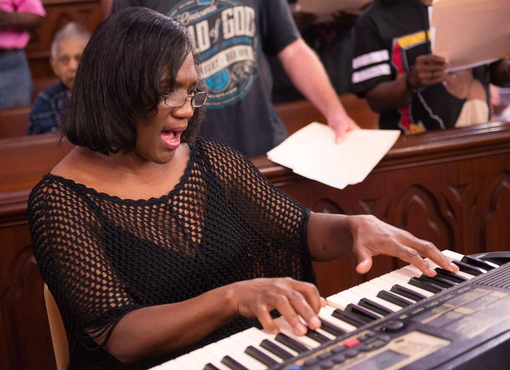 Deborah Cox plays the keyboard as she along with the House of Mercy Gospel Choir.