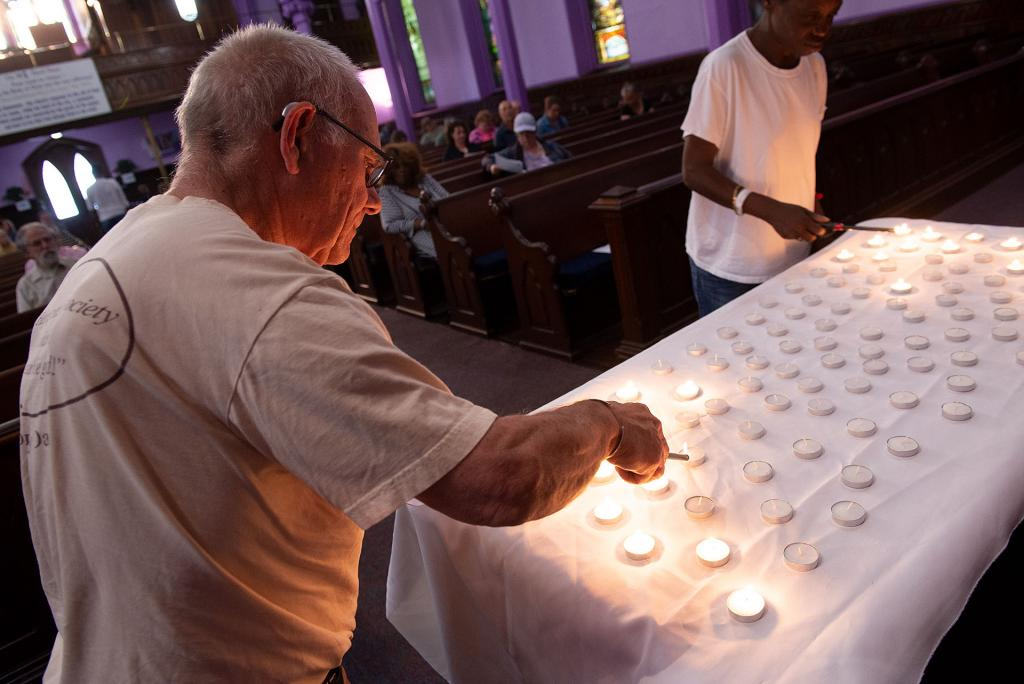 Tom Malthaner lights a candle during the service.