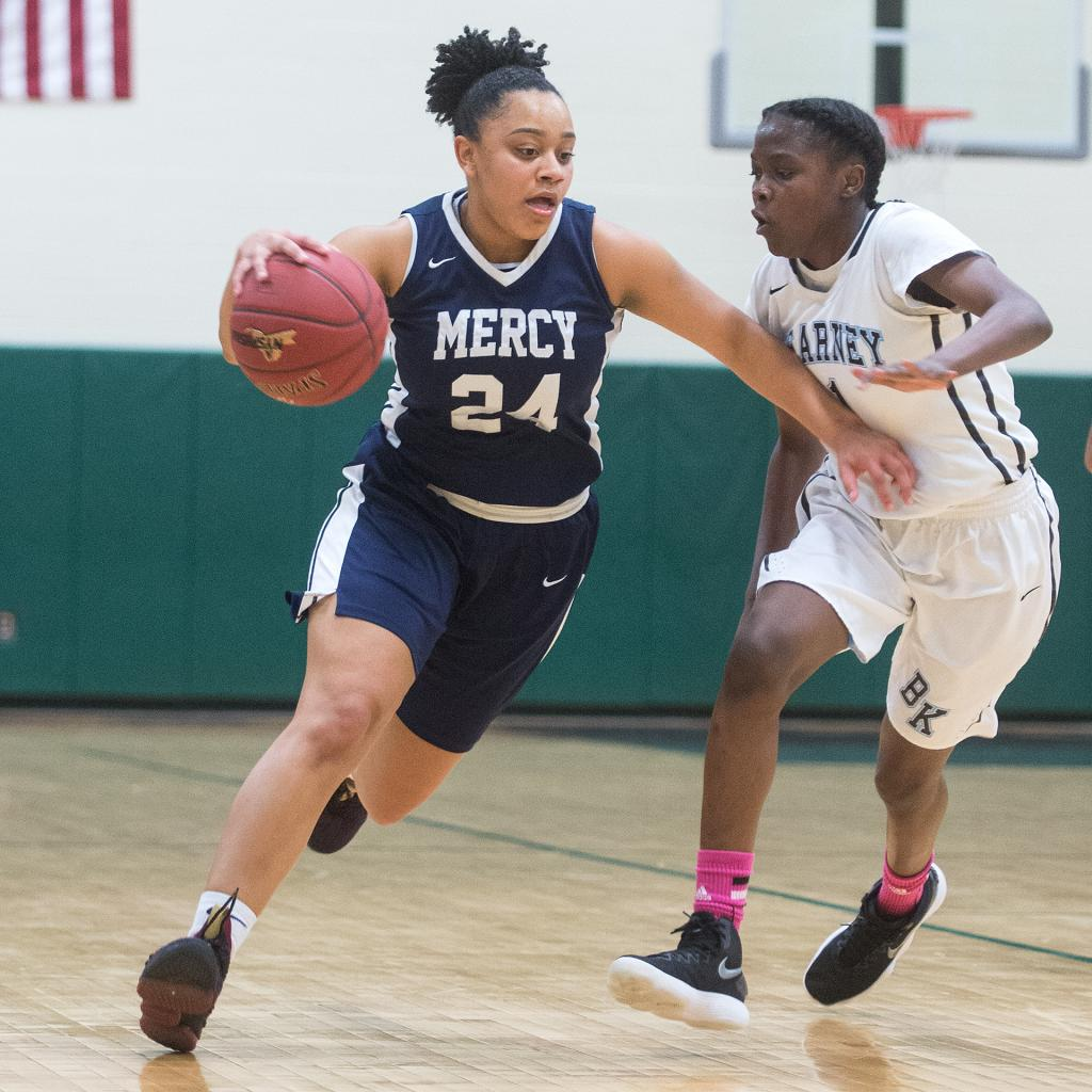 Mercy's Traiva Breedlove (24) brings the ball down court as she holds off Bishop Kearney's Lytoya Baker (1) in the first quarter of the Section 5 Class AA sectional championship game March 3. (Courier Photo by John Haeger)