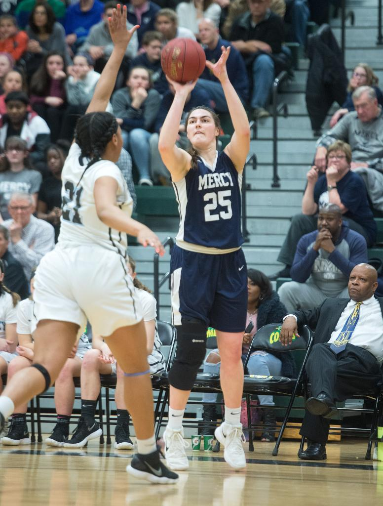 Mercy's Katie Titus (25) puts up a shot from the outside for three as Bishop Kearney's Saniaa Wilson (21) reaches in to defend in the second quarter of the Section 5 Class AA sectional championship game March 3. (Courier Photo by John Haeger)