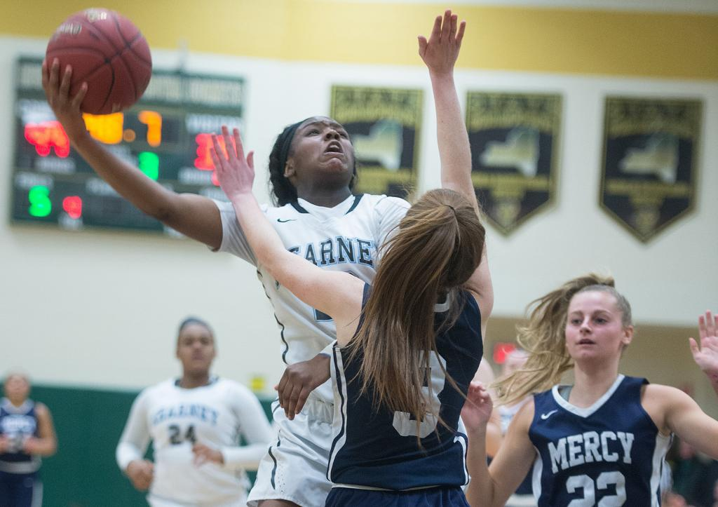 Bishop Kearney's Allure Simmons (23) goes up for two as Mercy's Alex Hetterich (3) defends in the fourth quarter of the Section 5 Class AA sectional championship game March 3. (Courier Photo by John Haeger)