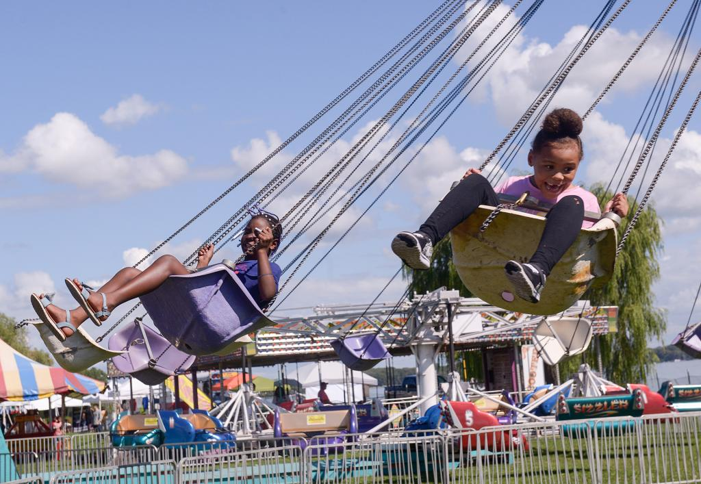 Festival participants ride on a swing during Festival Latino en Geneva Sept. 15. (Courier photo by John Haeger)