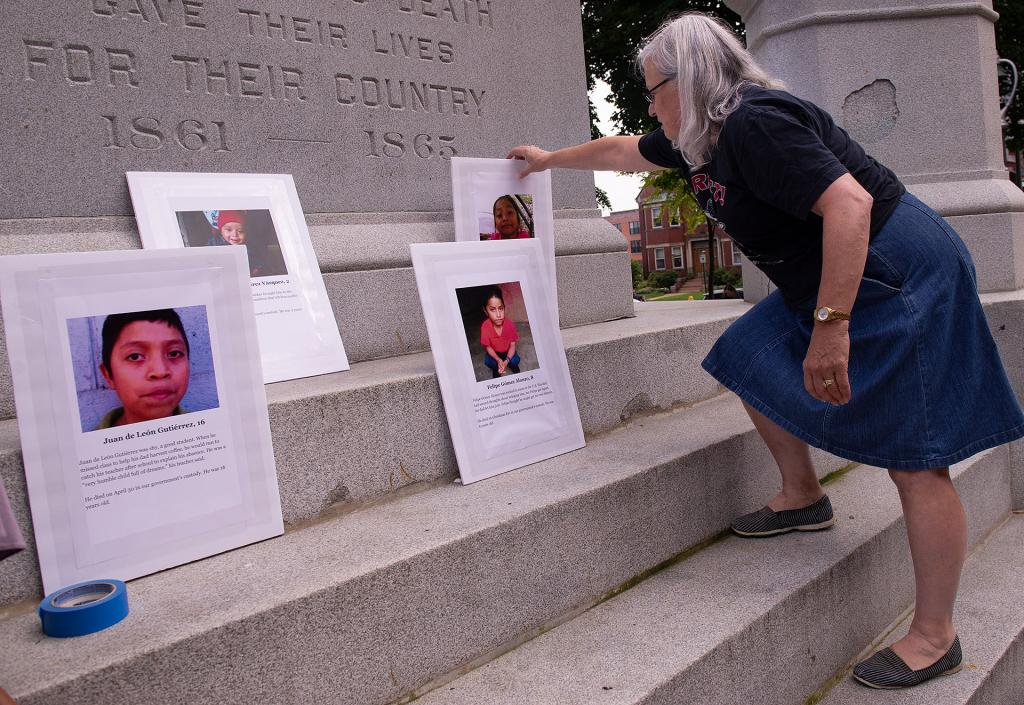 Before the start of the vigil, Ginny Hall arranges a display of pictures of the seven children who have died while in U.S. Border Patrol custody over the past 12 months.