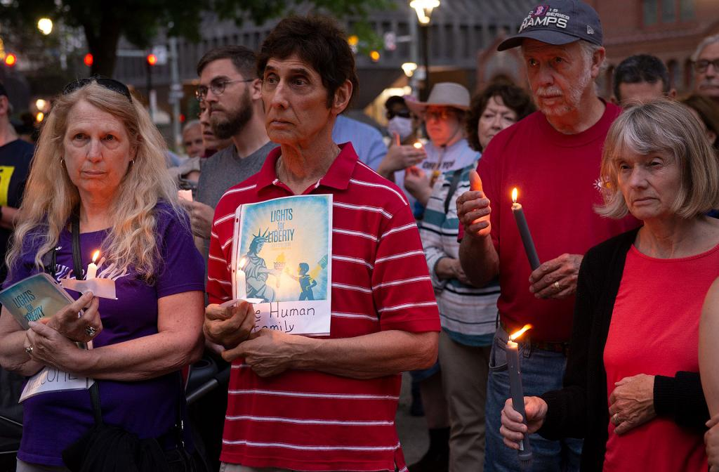 People hold candles during the vigil.
