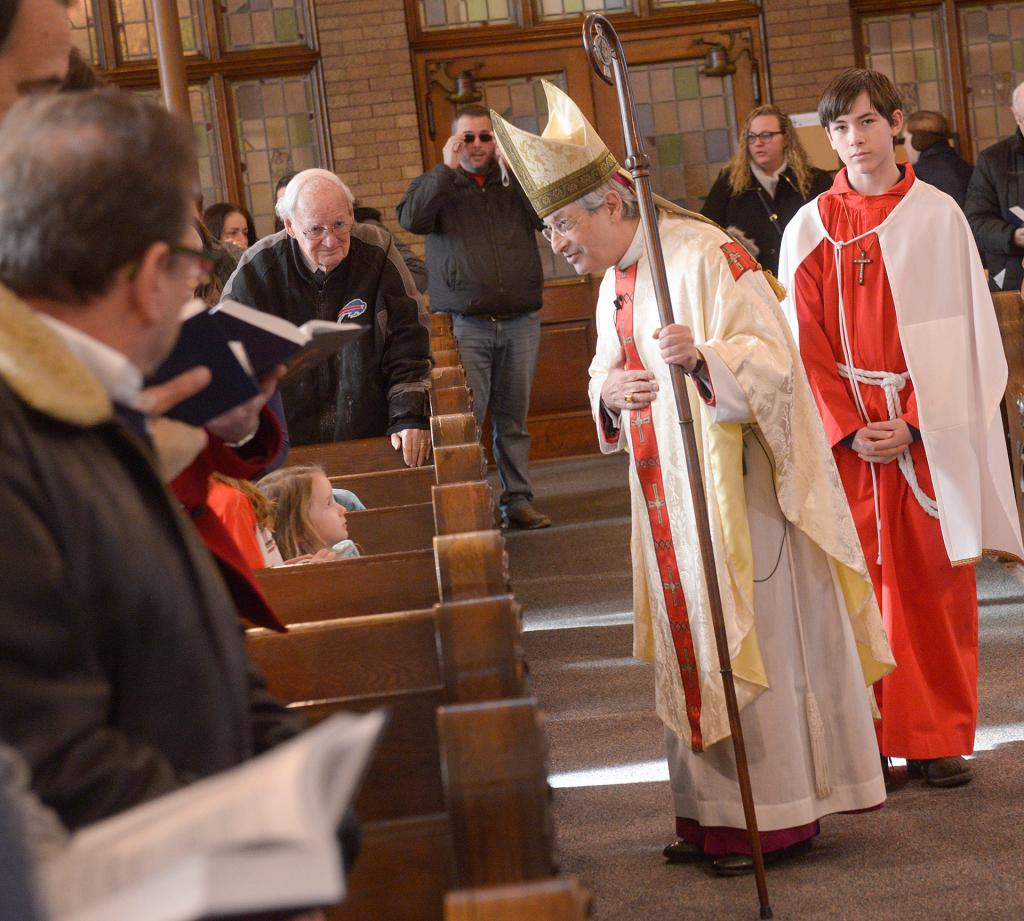 Bishop Matano greets Mass participants. (Courier photo by John Haeger)