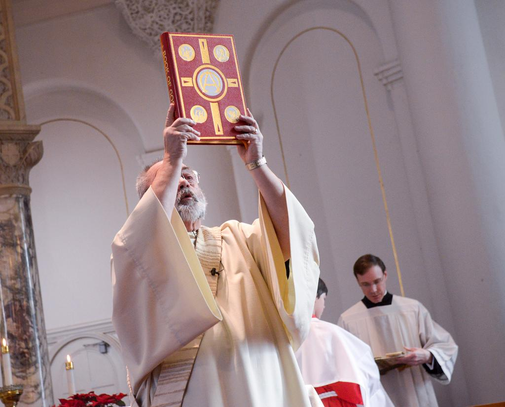 Deacon Claude Lester prepares to proclaim the Gospel. (Courier photo by John Haeger)