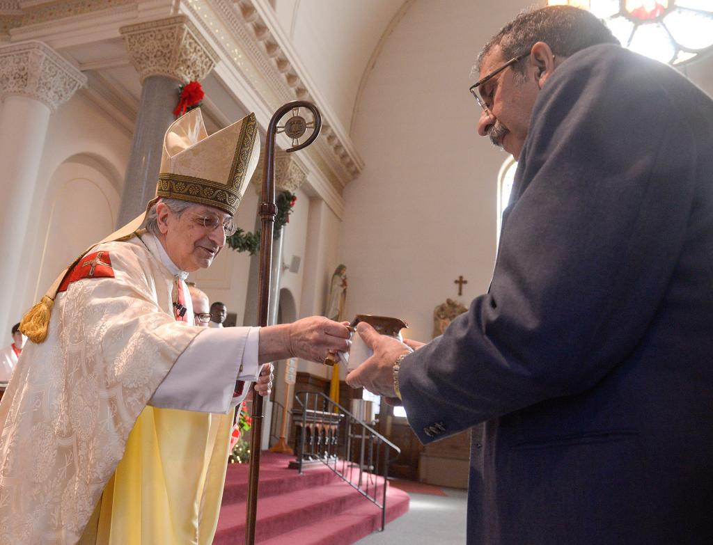 Bishop Matano receives the gifts from Joe Clement. (Courier photo by John Haeger)