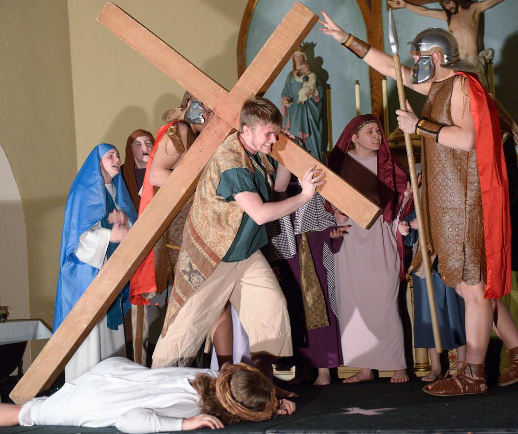 Thad Robertson as Simon of Cyrene carries the cross for Jesus at the fifth station.
