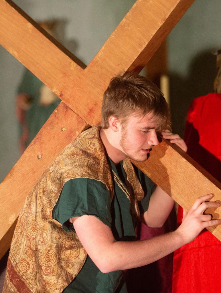 Simone of Cyrene carries Jesus' cross.