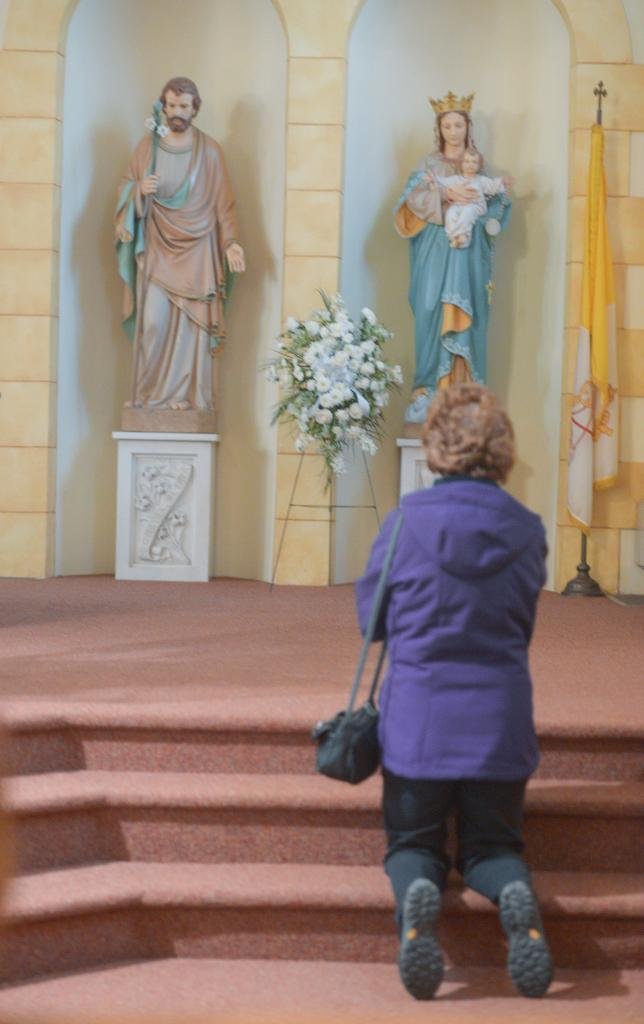A person prays March 13 at Holy Family Church in Auburn during the Day of Penance and Mercy.<br />