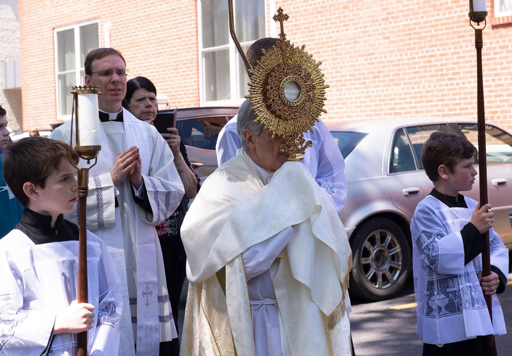 Bishop Matano carries the Eucharist.