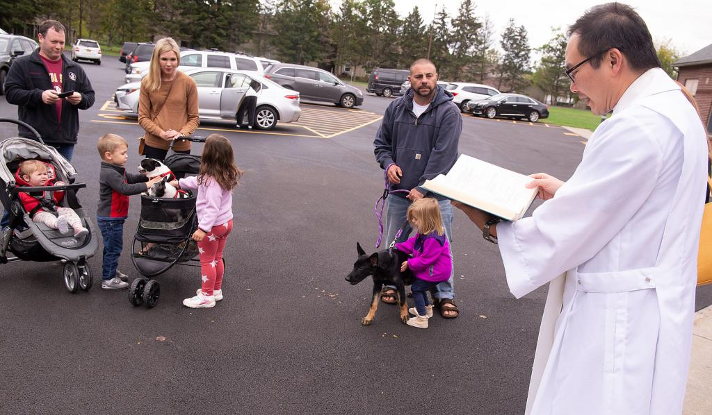 Father Edison Tayag, pastor at St. Patrick Church in Victor, blesses pets at the church Oct. 4.