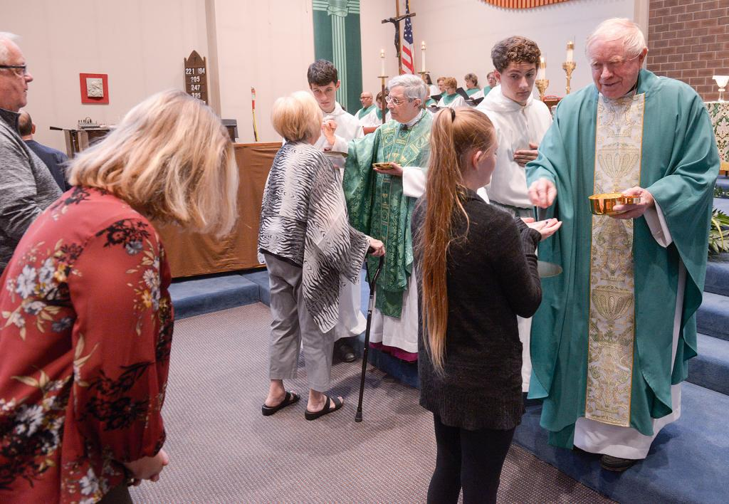 Bishop Salvatore R. Matano and Father James Schwartz distribute Communion during the Mass.(Courier Photo by John Haeger)