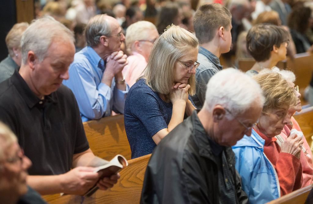 People pray during the Mass.(Courier Photo by John Haeger)