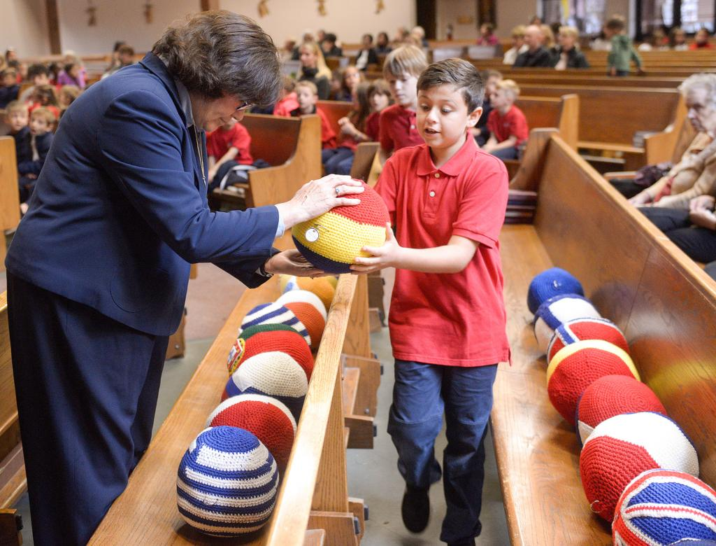 Gina Mangiamele hands St. Lawrence School student John Kilburyin a bead from The Giant Mary Queen of Peace International Rosary.(Courier Photo by John Haeger)